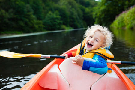 Happy kid enjoying kayak ride on beautiful river. Little curly toddler boy kayaking on hot summer day. Water sport and camping fun. Canoe for children. Funny child with vessel in a boat. Stock Photo