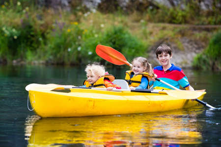 Happy family with three kids enjoying kayak ride on beautiful river. Little girl, toddler boy and teenager kayaking on hot summer day. Water sport and camping fun. Canoe and boat for children.
