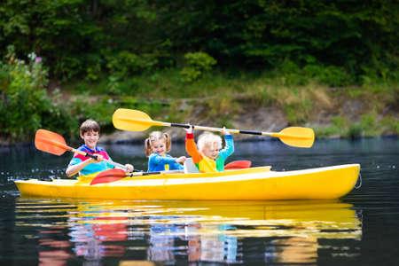 Gelukkig gezin met drie kinderen genieten van kajak ritje op prachtige rivier. Meisje, peuter jongen en tiener kajakken op hete zomerdag. Watersport en kamperen plezier. Kano en boot voor kinderen.