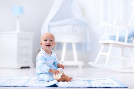 tomando leche: Adorable baby boy playing on a blue floor mat and drinking milk from a bottle in a white sunny nursery with rocking chair and bassinet. Bedroom interior with infant crib. Formula drink for infant. Foto de archivo