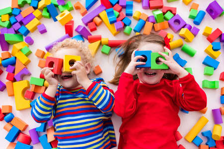 Happy preschool age children play with colorful plastic toy blocks. Creative kindergarten kids build a block tower. Educational toys for toddler or baby. Top view from above. Stockfoto