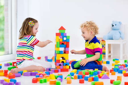 infant school: Happy preschool age children play with colorful plastic toy blocks. Creative kindergarten kids build a block tower. Educational toys for toddler or baby. Siblings having fun playing together. Stock Photo