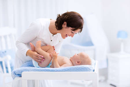 Young mother taking care of little boy in white sunny nursery with changing table, baby crib and rocking chair. Diaper change and clothing. Mom and son in beautiful bedroom at home. Archivio Fotografico