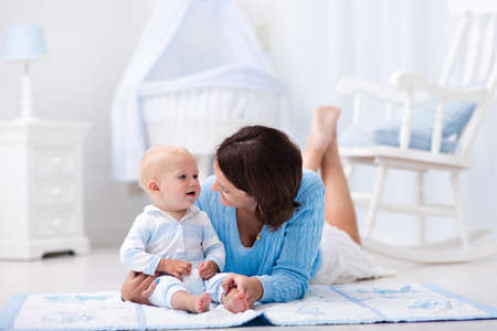 playmat: Happy young mother and adorable baby boy playing on a blue floor mat in a white sunny nursery with rocking chair and bassinet. Bedroom interior with infant crib. Mom and child on playmat at kids bed. Stock Photo