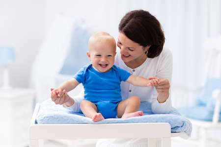 diaper changing table: Young mother taking care of little boy in white sunny nursery with changing table, baby crib and rocking chair. Diaper change and clothing. Mom and son in beautiful bedroom at home. Stock Photo