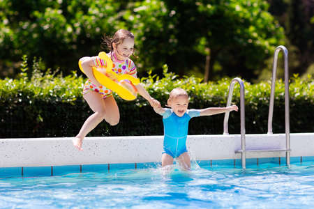 focus on: Happy little girl and boy holding hands jumping into outdoor swimming pool in a tropical resort during family summer vacation. Kids learning to swim. Focus on boy.
