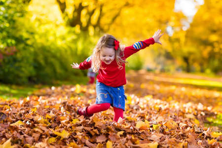 Happy little girl playing in beautiful autumn park on warm sunny fall day. Kids play with golden maple leaves. Фото со стока