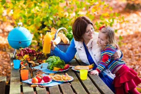 autumn garden: Happy young mother with little girl grilling meat and making sandwich and salad on a picnic table in sunny autumn park. Barbeque fun for parents with kids on warm fall day. Grill and BBQ party. Stock Photo
