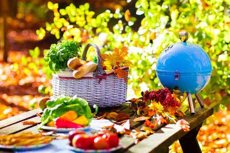 Tabela ustawiony na obiad na świeżym powietrzu w pięknym, słonecznym parku jesienią. Grill węglowy i kosz piknikowy z Bagietka chleb, kanapki, owoce i warzywa. Gotowanie na grilla i grill party w upadku.
