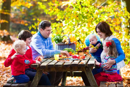 picnic table: Happy young family with four children grilling meat and making sandwich and salad on a picnic table in sunny autumn park. Barbeque fun for parents with kids on warm fall day. Grill and BBQ party.