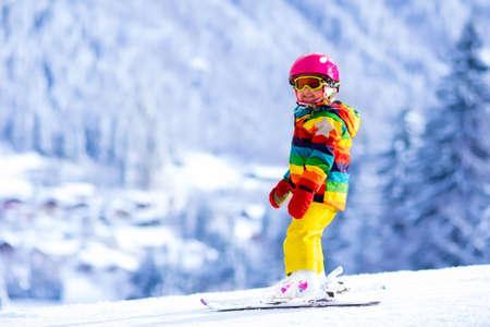 Kind skiën in de bergen. Actieve peuter jongen met veiligheidshelm, veiligheidsbril en palen. Ski race voor jonge kinderen. Wintersport voor familie. Kids ski les in alpine school. Weinig skiër racen in de sneeuw Stockfoto - 61224352