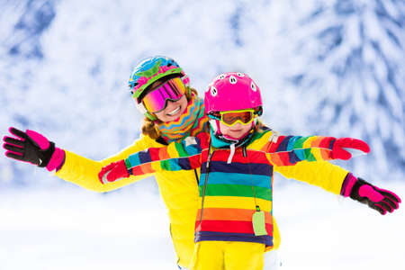 to ski: Mother and little child skiing in Alps mountains. Active mom and toddler kid with safety helmet, goggles and poles. Ski lesson for young children. Winter sport for family. Little skier racing in snow