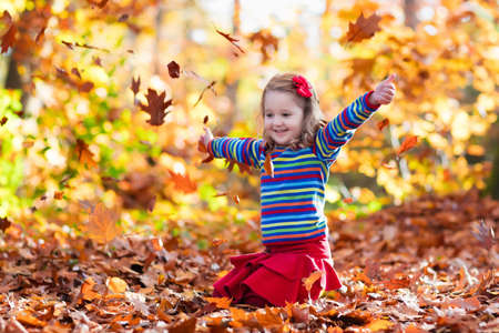 Happy little girl playing in beautiful autumn park on warm sunny fall day. Kids play with golden maple leaves. Stock Photo
