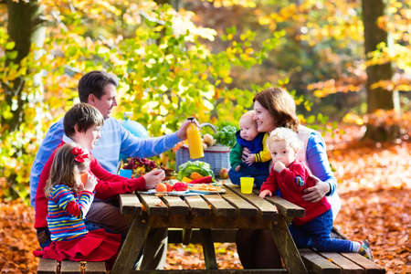 Happy young family with four children grilling meat and making sandwich and salad on a picnic table in sunny autumn park. Barbeque fun for parents with kids on warm fall day. Grill and BBQ party.