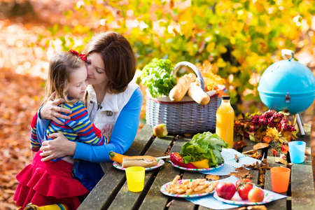 Happy young mother with little girl grilling meat and making sandwich and salad on a picnic table in sunny autumn park. Barbeque fun for parents with kids on warm fall day. Grill and BBQ party.
