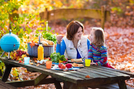 picnic table: Happy young mother with little girl grilling meat and making sandwich and salad on a picnic table in sunny autumn park. Barbeque fun for parents with kids on warm fall day. Grill and BBQ party. Stock Photo