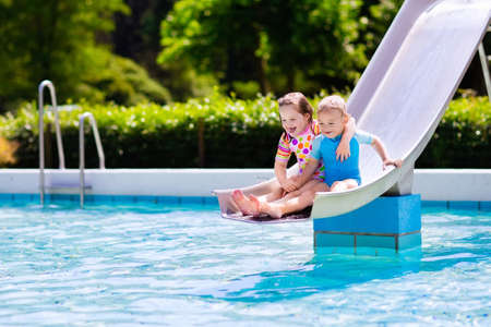 niñas pequeñas: Feliz niño pequeño y una niña juegan en diapositiva de agua en la piscina al aire libre en un día caluroso de verano. Los niños aprenden a nadar. Los niños que usan protección solar deslizante guardia de erupción en la aguamarina parque infantil en el centro turístico tropical Foto de archivo