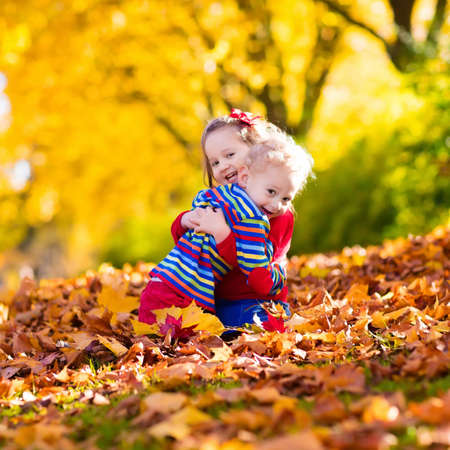hermanos jugando: Happy children playing in beautiful autumn park on warm sunny fall day. Kids play with golden maple leaves. Foto de archivo