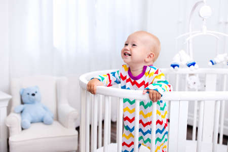 baby bed: Cute laughing baby standing in bed after nap time. Nursery interior for young kids. Adorable little boy playing in his crib. White furniture for children bedroom.