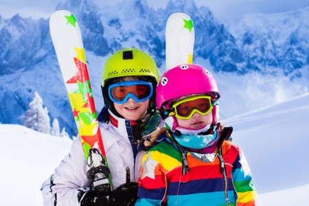 Jongen en meisje skiën in de bergen. Peuter kind en tiener met helm, bril, polen. Ski-race voor kinderen. Wintersport voor familie. Kids ski les in alpine school. Weinig skiër racen in de sneeuw Stockfoto