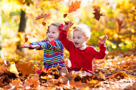 autumn garden: Happy children playing in beautiful autumn park on warm sunny fall day. Kids play with golden maple leaves. Focus on girl. Stock Photo