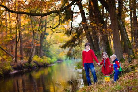 dia soleado: niños felices jugando en la orilla del río en un hermoso parque del otoño en día cálido y soleado de la caída. Los niños juegan con las hojas de arce de oro. Foto de archivo