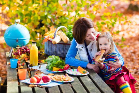 lunch table: Happy young mother with little girl grilling meat and making sandwich and salad on a picnic table in sunny autumn park. Barbeque fun for parents with kids on warm fall day. Grill and BBQ party. Stock Photo