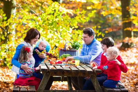 personas comiendo: Familia joven feliz con cuatro hijos asar la carne y hacer sándwich y ensalada en una mesa de picnic en el parque soleado de otoño. diversión barbacoa para los padres con niños en el día caliente de la caída. Parrilla y fiesta de barbacoa. Foto de archivo