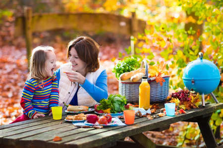 Happy young mother with little girl grilling meat and making sandwich and salad on a picnic table in sunny autumn park. Barbeque fun for parents with kids on warm fall day. Grill and BBQ party. Stock Photo