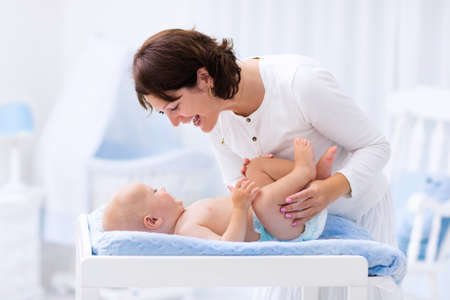 Junge Mutter des kleinen Jungen in weißen sonnigen Kinderzimmer mit Wickeltisch, Kinderbett und Schaukelstuhl zu kümmern. Windelwechsel und Kleidung. Mutter und Sohn in schönen Schlafzimmer zu Hause. Standard-Bild