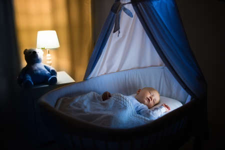 Adorable baby sleeping in blue bassinet with canopy at night. Little boy in pajamas taking a nap in dark room with crib, lamp and toy bear. Bed time for kids. Bedroom and nursery interior. Banque d'images