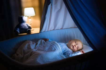Adorable baby sleeping in blue bassinet with canopy at night. Little boy in pajamas taking a nap in dark room with crib, lamp and toy bear. Bed time for kids. Bedroom and nursery interior. Stock Photo