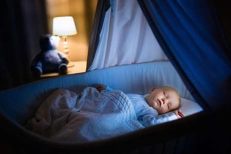 Adorable bebé durmiendo en la cuna azul con dosel en la noche. El niño pequeño en pijama tomando una siesta en una habitación oscura con el pesebre, la lámpara y el juguete. la hora de dormir para los niños. Dormitorio y cuarto de niños interior. Foto de archivo