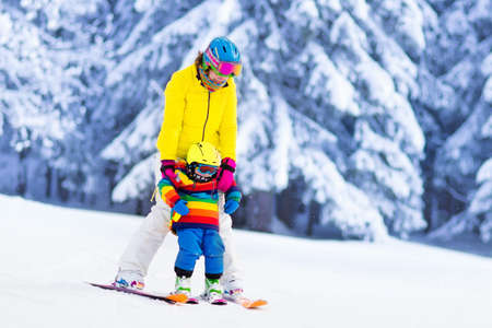 family playing: Mother and little child skiing in Alps mountains. Active mom and toddler kid with safety helmet, goggles and poles. Ski lesson for young children. Winter sport for family. Little skier racing in snow