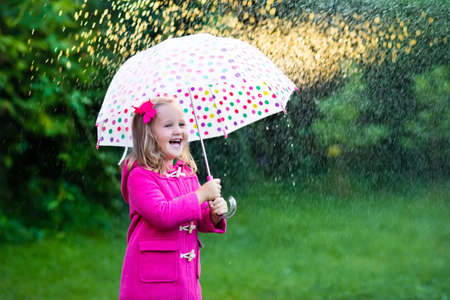 rain weather: Little girl playing in rainy summer park. Child with colorful rainbow umbrella, pink coat walking in the rain. Kid having fun in autumn shower. Outdoor activity by any weather
