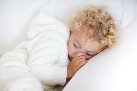 Leuke blonde krullende kleine jongen slapen op witte bank. Mooie peuter die een dutje doet met warme witte pyjama's die zijn duim zuigen.