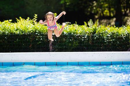 schwimmring: Glückliches kleines Mädchen in Außenpool in einem tropischen Resort während der Familiensommerferien zu springen. Kinder lernen zu schwimmen. Wasserspaß für Kinder. Lizenzfreie Bilder