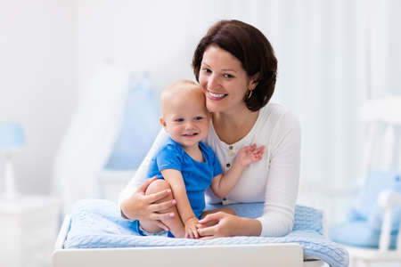 changing diaper: Young mother taking care of little boy in white sunny nursery with changing table, baby crib and rocking chair. Diaper change and clothing. Mom and son in beautiful bedroom at home. Stock Photo