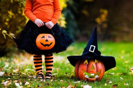 Niña en traje de la bruja que juega en parque del otoño. Niño que se divierte en el truco o. Los niños truco o trato. niño niño pequeño con jack-o-lantern. Los niños con cubo de caramelo en el bosque de otoño. Foto de archivo - 62375420