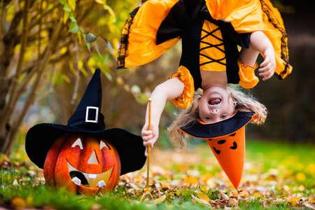 Petite fille en costume de sorcière jouant dans le parc de l'automne. Enfant amusant à jouer Halloween ou traiter. Les enfants des bonbons ou un traitement. kid enfant avec jack-o-lantern. Les enfants avec des bonbons seau dans la forêt d'automne. Banque d'images - 61813299
