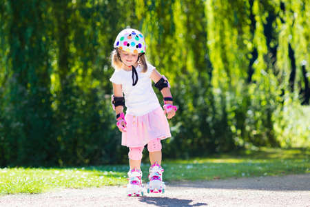 knee pads: Little girl learning to roller skate in sunny summer park. Child wearing protection � elbow and knee pads, wrist guards and safety helmet for safe roller skating ride. Active outdoor sport for kids.