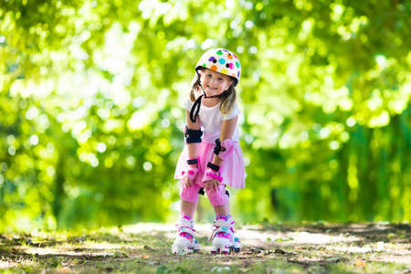 knee pads: Little girl learning to roller skate in sunny summer park. Child wearing protection elbow and knee pads, wrist guards and safety helmet for safe roller skating ride. Active outdoor sport for kids. Stock Photo