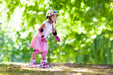 roller blade: Little girl learning to roller skate in sunny summer park. Child wearing protection elbow and knee pads, wrist guards and safety helmet for safe roller skating ride. Active outdoor sport for kids. Stock Photo