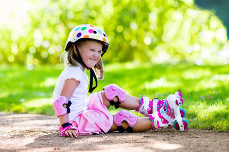 zapatos de seguridad: Niña que aprende a patinar en el parque soleado de verano. Niño que lleva el codo protección y rodilleras, muñequeras y casco de seguridad para una conducción segura de patinaje sobre ruedas. deporte al aire libre para los niños activos.