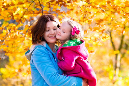 hold on: Mother and daughter play in autumn park. Parent and child walk in the forest on a sunny fall day. Children playing outdoors with yellow maple leaf. Toddler girl picking golden leaves. Mom hugging kid. Stock Photo