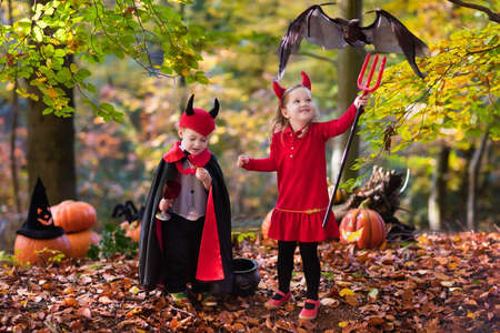 Two funny kids wearing devil and vampire costume with red horns and trident trick or treating on Halloween. Children dressed up as witch play in autumn park. Stock Photo