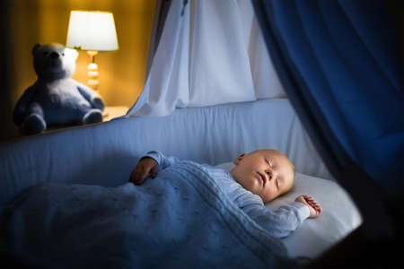 Adorable baby sleeping in blue bassinet with canopy at night. Little boy in pajamas taking a nap in dark room with crib, lamp and toy bear. Bed time for kids. Bedroom and nursery interior. 免版税图像