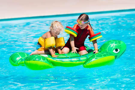 float: Happy little girl and boy playing in outdoor swimming pool sitting on inflatable toy turtle in a tropical resort during family summer vacation. Kids learning to swim. Stock Photo