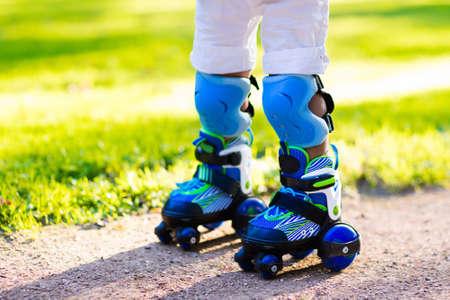 El pequeño niño que está aprendiendo a patinar en el parque de verano. Los niños llevaban almohadillas de protección para el paseo de patinaje sobre ruedas segura. deporte al aire libre para los niños activos. Cierre de vista de los patines.