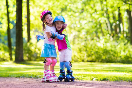elbow pads: Girl and boy learn to roller skate in summer park. Children wearing protection pads and safety helmet for safe roller skating ride. Active outdoor sport for kids. Siblings help and support each other